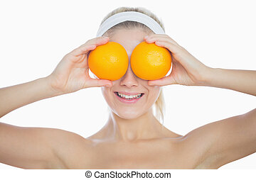 Happy woman holding oranges in front of eyes
