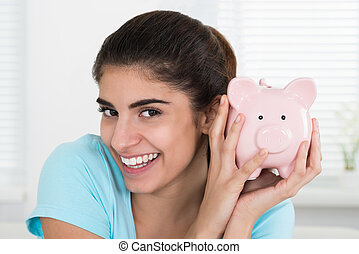Happy Woman Holding Piggy Bank At Home