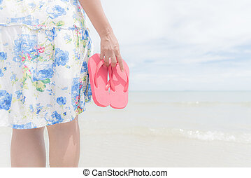 Happy woman holding pink flip flop on sandy beach for summer holiday and vacation concept.