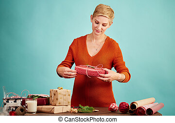 Happy woman holding red present box, ready for Christmas greetings