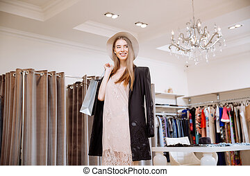 Happy woman holding shopping bags and standing in clothing store