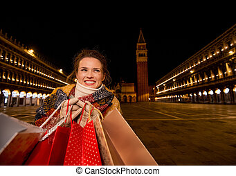 Happy woman holding shopping bags on Piazza San Marco in evening