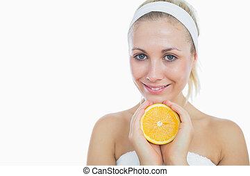 Happy woman holding slice of orange