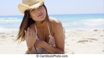 Happy woman holding something while on the beach