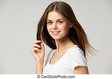 Happy woman holds hand near hair and smiling close up