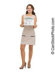 Happy woman homeowner showing scale model of house
