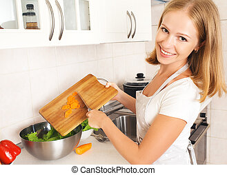 happy woman housewife preparing salad in the kitchen