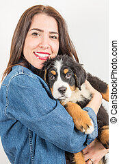happy woman huge a puppy of bernese mountain dog