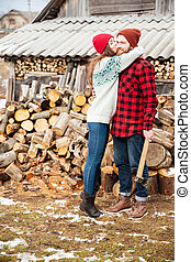 Happy woman hugging handsome man with axe in village -...