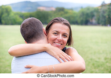 Happy woman hugging her boyfriend outdoor in a park