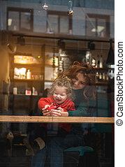 Happy woman hugging her little daughter indoors