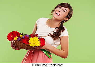 Happy woman in a basket of spring flowers