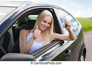 Happy Woman In A Car Showing A Key And Gesturing Thumb Up