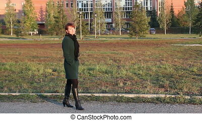 Happy woman in a dark coat walking outdoors