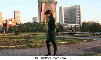 Happy woman in a dark green coat waiting outdoors