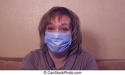 Happy woman in a medical mask is looking at the camera and talking