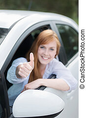 Happy woman in a new car giving a thumbs up