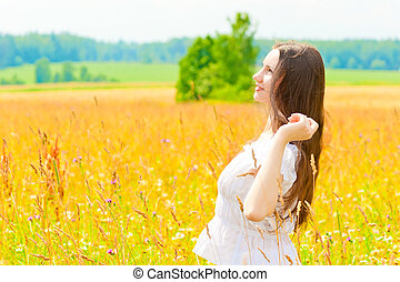 happy woman in a white sundress in the field
