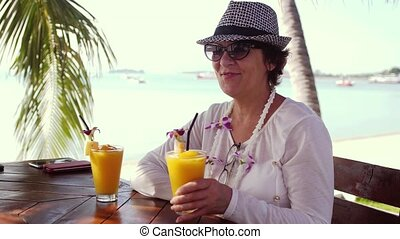 Happy woman in aged wearing sunglasses and hat drinking fresh orange juice with straw on beach cafe during summer holidays.