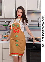 woman in apron with cupcakes in kitchen