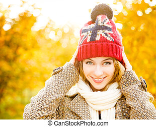 Happy Woman in Beanie Hat on Autumn Background
