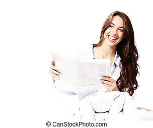 happy woman in bed with a newspaper on white background