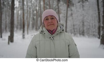 Happy woman in beige coat and pink cap slowly walking in the forest through the trees, breathing fresh air and looking at the camera. Aged female traveller spending her time strolling in winter wood.