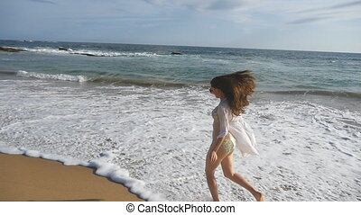 Happy woman in bikini and shirt running on the ocean waves at the beach. Young beautiful girl enjoying life and having fun at sea shore. Summer vacation or holiday. Slow motion Close up