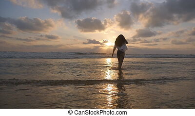 Happy woman in bikini and shirt walking at the ocean water on the beach at sunset. Young beautiful girl enjoying vacation and having fun at sea shore at sunrise. Summer holiday. Slow motion