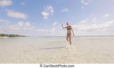 Happy woman in bikini running on clear water on sea beach...