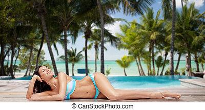 happy woman in bikini tanning over summer beach - people,...