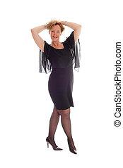 Happy woman in black dress standing.