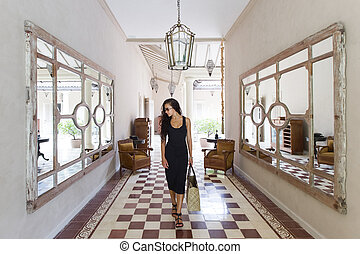 Happy woman in black dress with straw bag in mall with white walls and columns