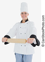 Happy woman in chef clothing holding rolling pin