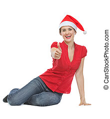 Happy woman in Christmas hat sitting on floor and showing thumbs up
