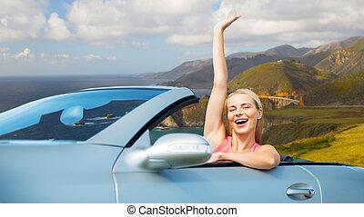 happy woman in convertible car on big sur coast