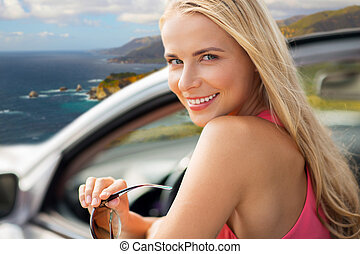 happy woman in convertible car over big sur coast