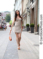 Happy woman in dress on the street