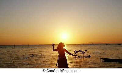 Happy woman in dress running on the beach spinning around in slow motion raising arms enjoying freedom during sunset. holidays vacation travel.