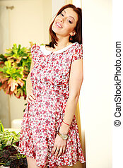 Happy woman in dress standing at home