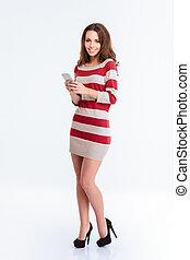 Happy woman in dress using smartphone