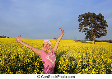 Happy woman in field of golden canola