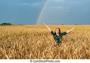 Happy woman in field with wheat hands in sides