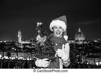happy woman in Florence with Christmas tree showing thumbs up