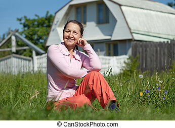 Happy woman in front of home