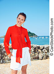 Happy woman in front of scenery overlooking lagoon with ...
