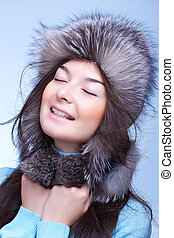 happy woman in fur cap on the blue background