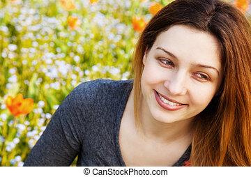 Happy woman in garden full of flowers