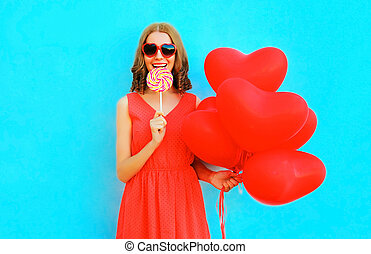 Happy woman in hat with a lollipop candy, air balloons on blue background