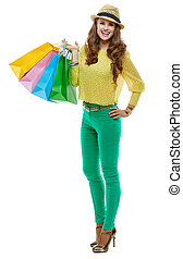 Happy woman in hat with shopping bags on white background